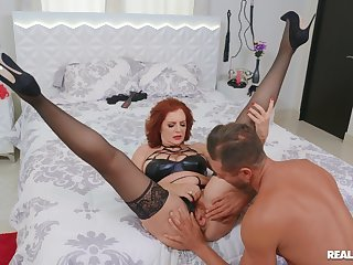Redhead busty model Andi James gets fucked balls deep on the bed